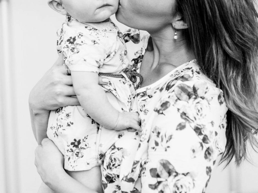 mom kissing daughter on cheek