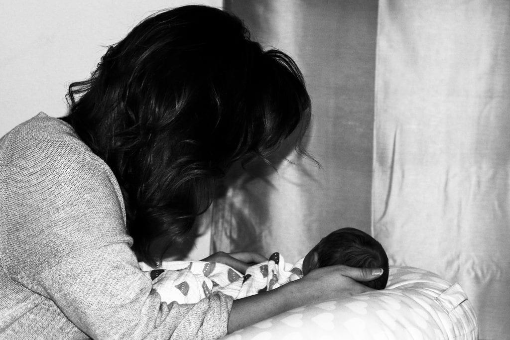 black and white photo of woman holding newborn baby