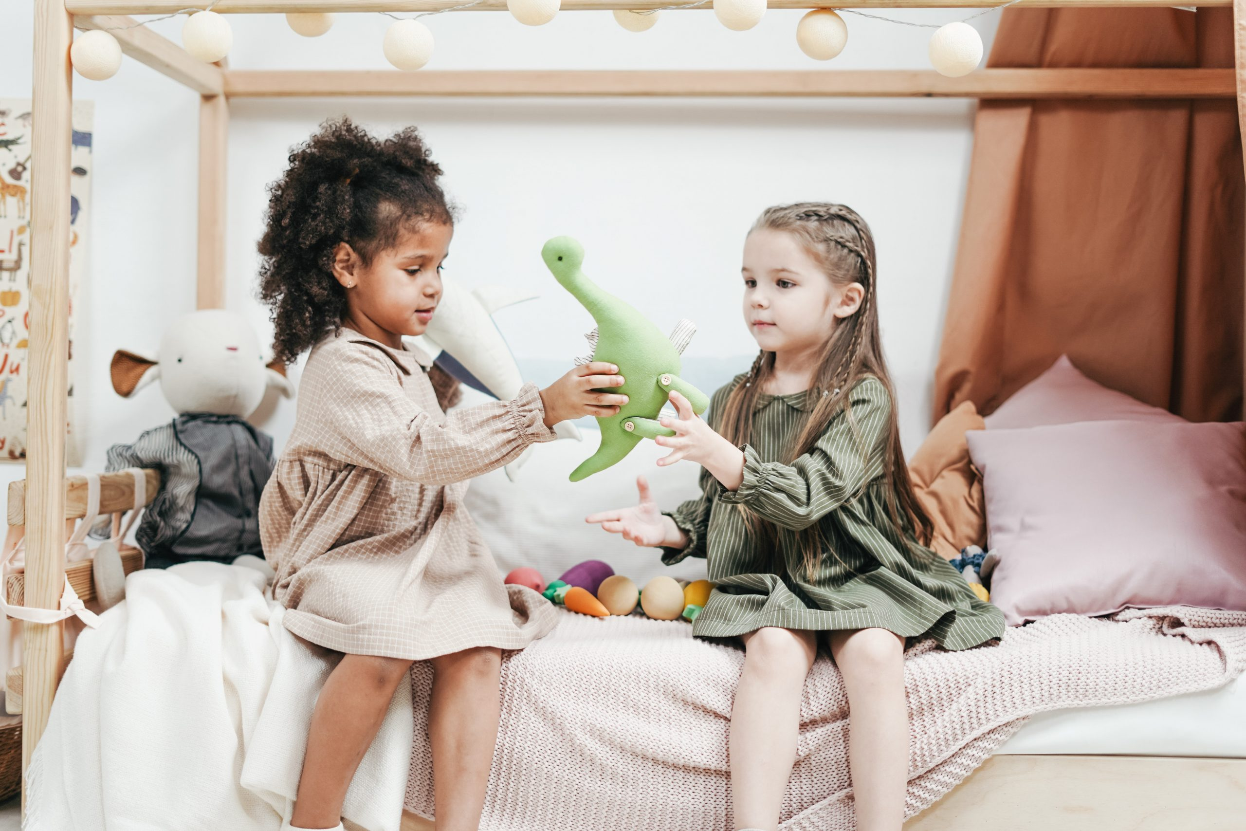 two little girls playing with a stuffed dinosaur