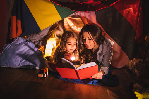 kid reading in dark with flashlight