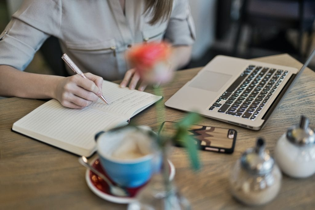 woman writing in journal by laptop with coffee