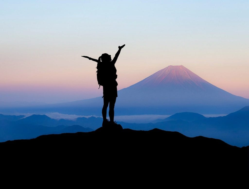 woman standing on mountaintop
