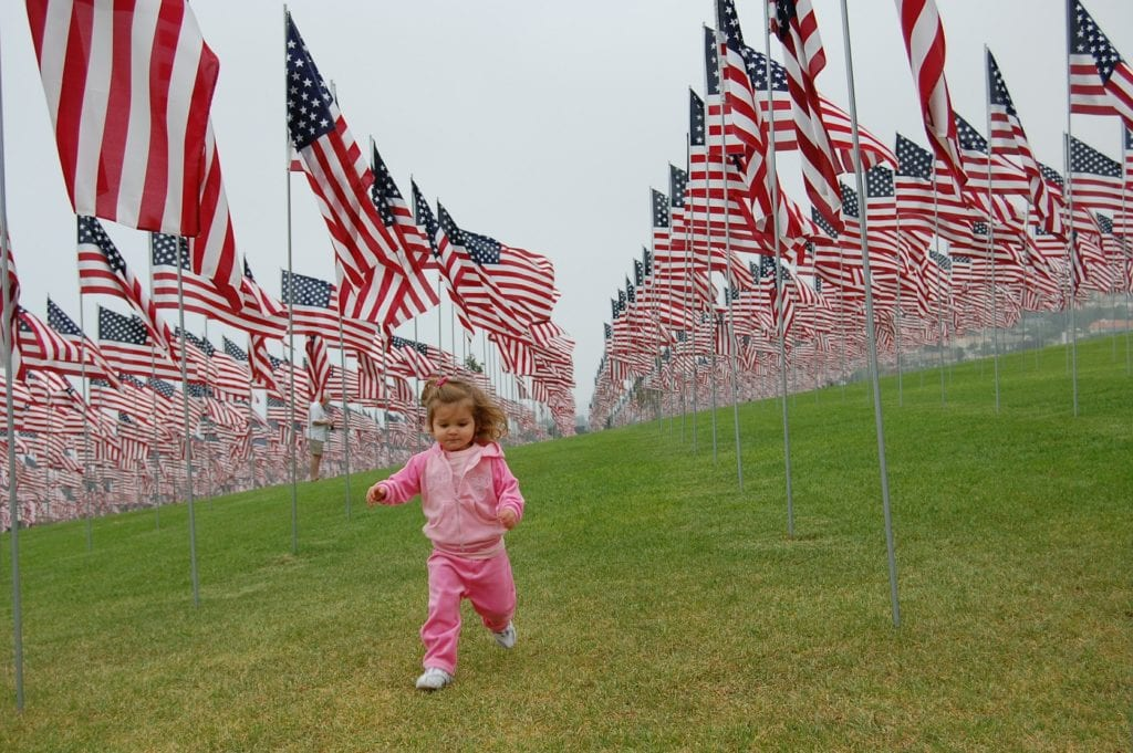 little girl running in fields of American flags